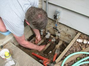 a technician checks the sprinkler line connections box